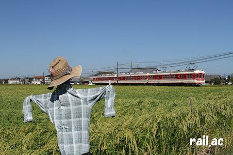 案山子に見送られて青空広がる田園を往く1000系列
