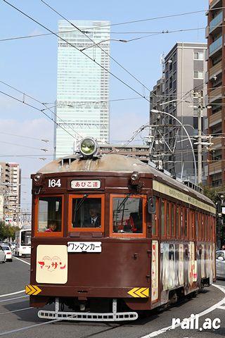 あべのハルカスをバックに走る阪堺電車モ164「マッサン」ラッピング