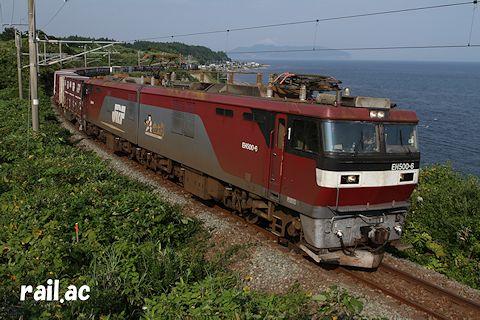 函館山を望む津軽海峡沿いを行くEH500 2次タイプ牽引貨物列車