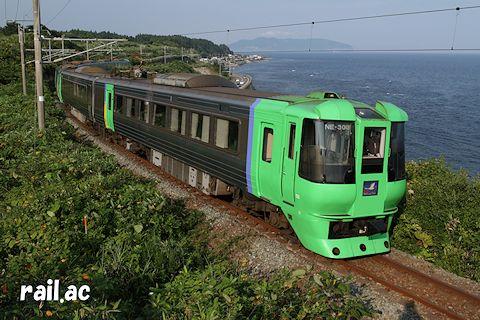 函館山を望む津軽海峡沿いを行く785系300番代先頭のスーパー白鳥